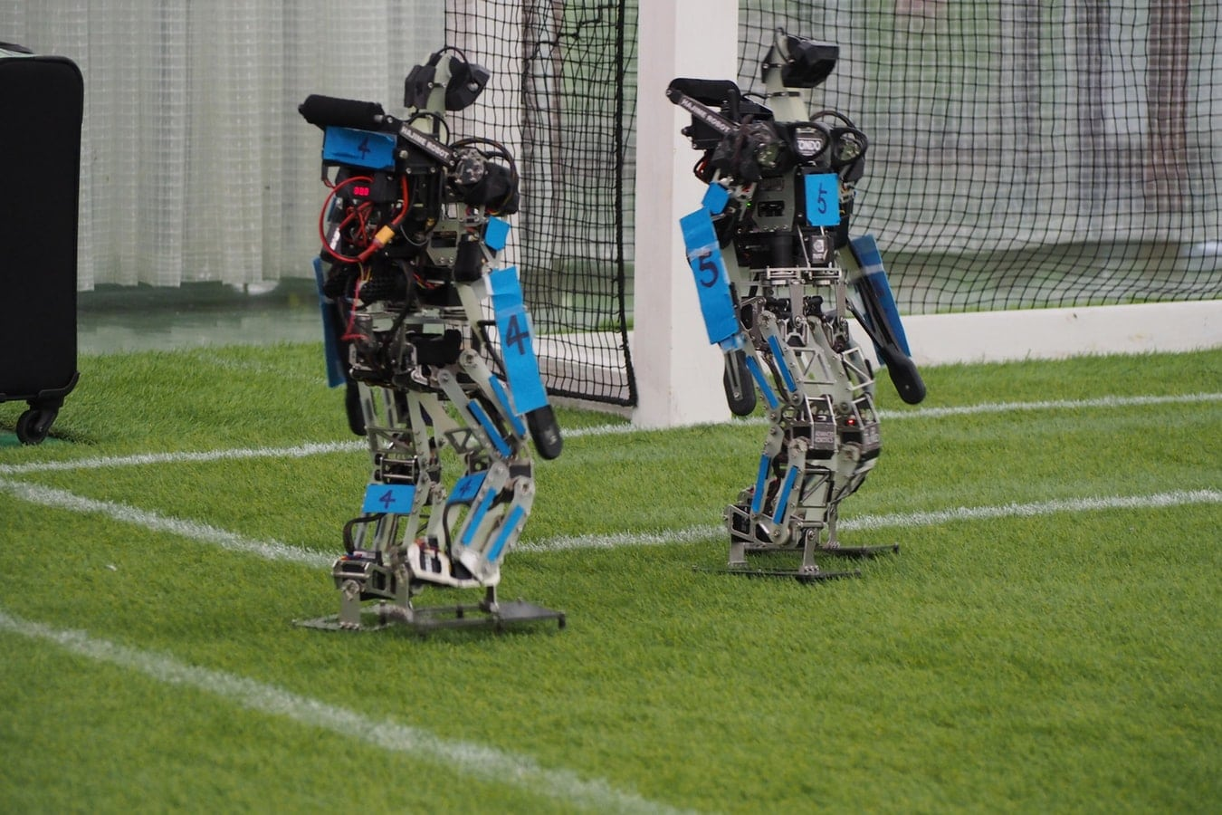 Zwei humanoide Roboter auf einem Fußballfeld